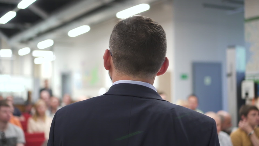 American businessman talking and mentoring colleagues at business conference in office room. Back view of entrepreneur wearing suit is speaking for audience in company interior. Man and woman #1041704236