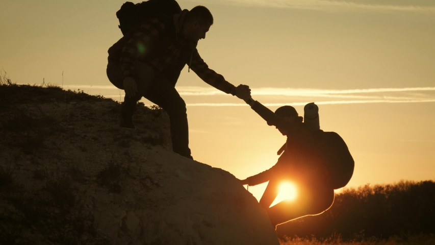 Silhouette of helping hand between two climber. two hikers on top of the mountain, a man helps a woman to climb a sheer stone. couple hiking help each other silhouette in mountains with sunlight. #1041721216