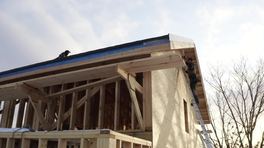 Panoramic view from below of wooden house under construction. Builder on ladder is covering the wooden house frame with plywood using hydraulic hammer. | Shutterstock HD Video #1041882856