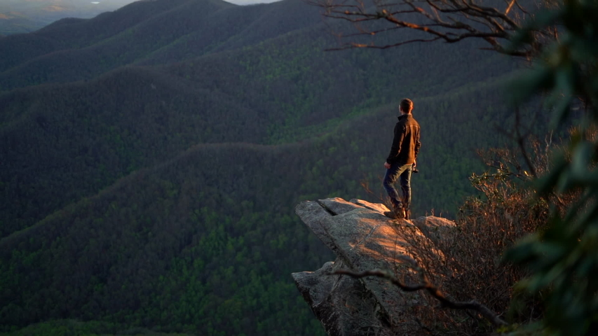 Hiking man is backlit by the setting sun as he stands on a cliff and looks out over the mountains and forest below | Shutterstock HD Video #1041905146