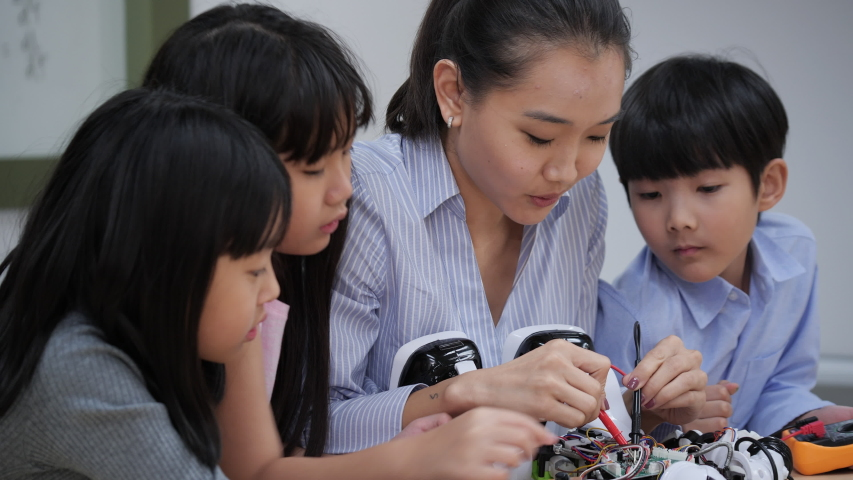 Asian woman teacher teaching and testing robotics responses in laboratory at school. Young architects kids design and demonstration circuit technology ideas and collaborating development robot.   Shutterstock HD Video #1041966856