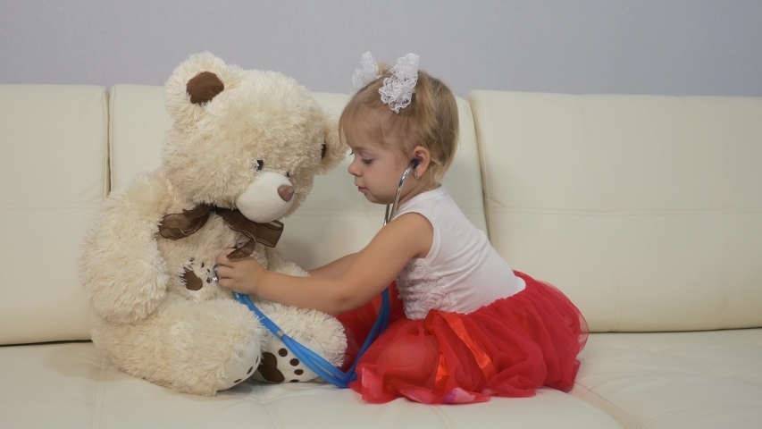 Little girl plays a doctor with a stethoscope and a teddy bear. girl sitting on the couch. The concept of children's fantasies and games. Training as a doctor