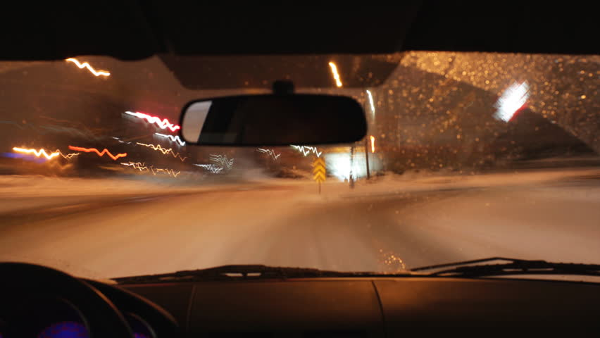Winter highway. Nighttime timelapse. Assembled from hi-res stills using a Canon 550D. Driver's eyes in rearview mirror. Highway 401, Toronto, Ontario.