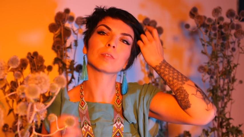 Portrait of a girl dancing in a hippie nightclub. Nearby grow wild plants.   Shutterstock HD Video #1042192606