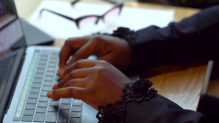 African american businesswoman working with laptop and papers. Busy woman paying bills online banking managing finances checking budget doing paperwork using computer sitting at desk   Shutterstock HD Video #1042268866
