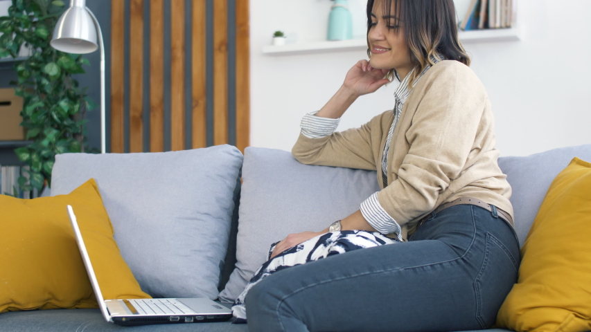 Young Woman Seat on Couch inn Modern Living Room and Using Laptop for Watching Video or Social Network. Lifestyle Concept. Happy Woman Relaxing at Home.   Shutterstock HD Video #1042271716
