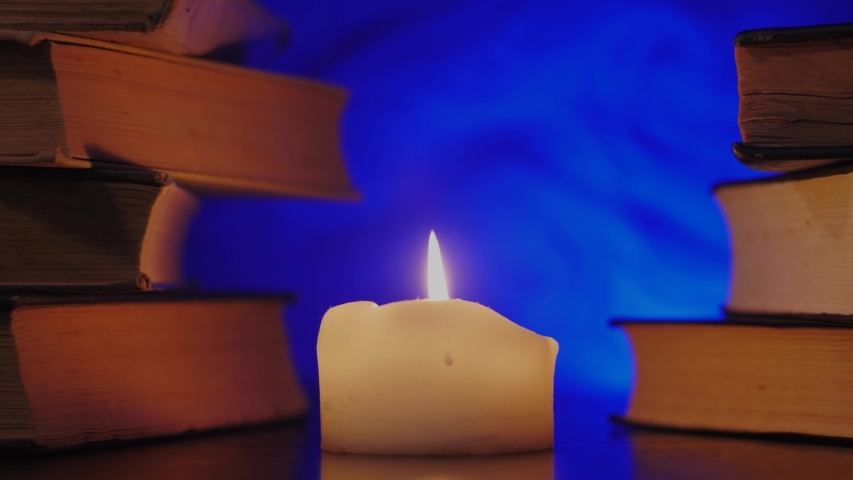 Piles of books are standing near a burning candle and colored magic smoke is flying.   Shutterstock HD Video #1042340386