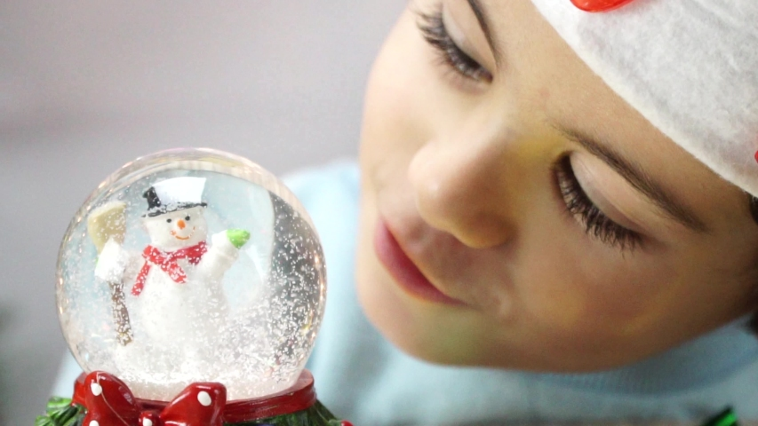 Little boy shook the snow globe, put it on the floor and peep inside it as the snow falls on the santa claus located inside this snow globe. 4K | Shutterstock HD Video #1042367296