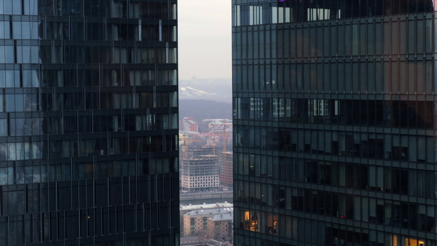 the camera pans on modern glass buildings and construction of high-rise buildings against the city background #1042405906