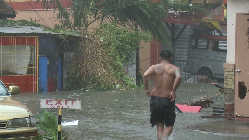 LEYTE, PHILIPPINES - NOVEMBER 2013: Person Walks Through Storm Surge Flooding After Major Hurricane Hits City
