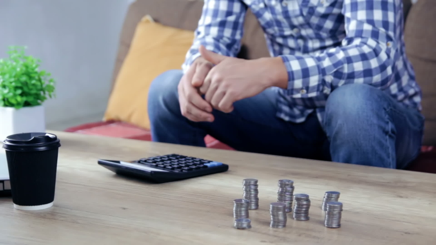 Worried man counting money on table, price inflation, low-paid job, savings   Shutterstock HD Video #1042534366
