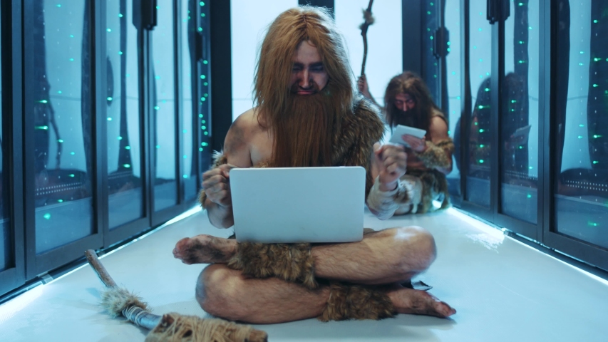 Primeval IT engineer using laptop computer discovering technology at modern database. Happy savage neanderthal dancing with joy having fun staying at data center. | Shutterstock HD Video #1042548616