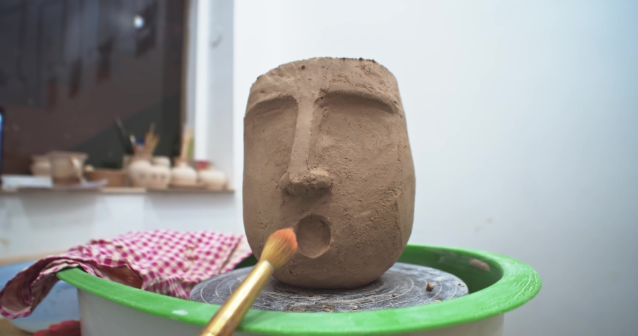 Artist created human face mask on flowerpot vase with clay on pottery cyrcle table in craft artist workshop. Modern art studio education. Ceramist presentating new ceramic object. Freelance business. | Shutterstock HD Video #1042593376
