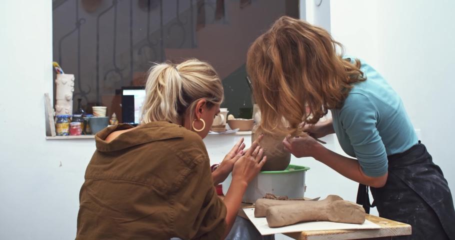 Female potter ceramist finished creating modern vase pot with human face in home workshop studio using laptop online. Art education courses. Artist educating lifestyle. Futuristic interior designer. | Shutterstock HD Video #1042593556