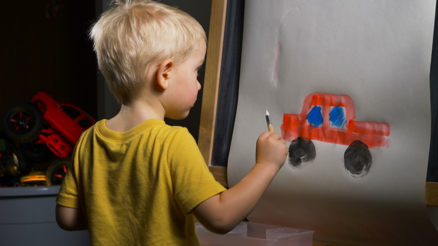 Little boy (preschooler) is painting a red toy truck with acrylic paint. Indoor kids activities, daycare, classroom. Early education concept, child creativity and art | Shutterstock HD Video #1042655656