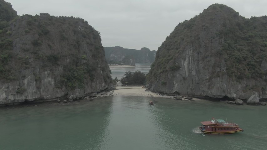 4k Aerial Drone Footage of An Island with 2 beaches front and back in Ha Long Bay, Lan Ha Bay, Vietnam in Cloudy Day. Small Boat are Transporting passengers to the Island. | Shutterstock HD Video #1042713916