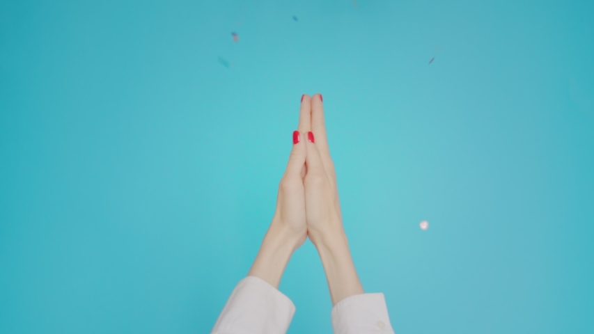 Woman hands clapping applause with festive confetti gesture isolated over blue background in studio. Copy space for advertisement. With place for text or image. Advertising area, mock up. | Shutterstock HD Video #1042727596