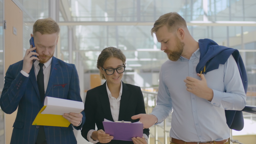 Group of young businesspeople looking at documents and discussing new startup while walking office hallway. Corpotare communications concept   Shutterstock HD Video #1042783666