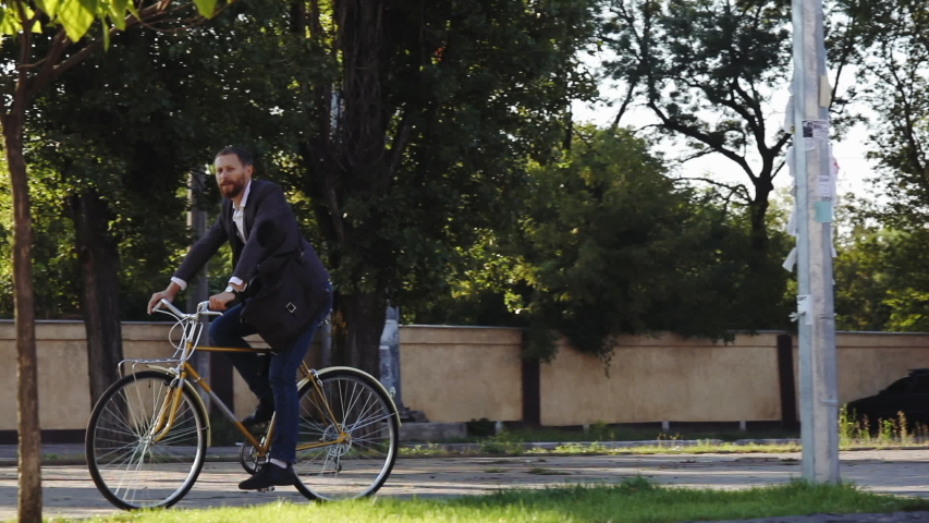 Bearded Businessman in business suit riding on retro bicycle to work on urban street in the morning on sunset | Shutterstock HD Video #1042796176