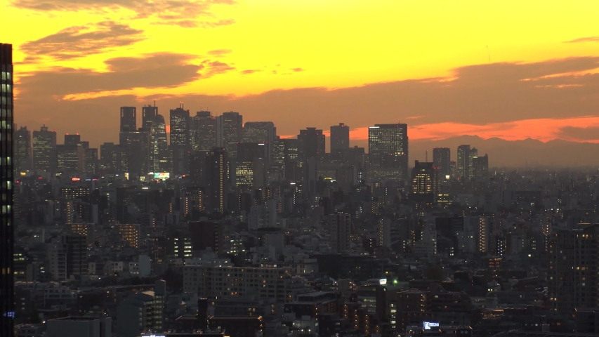 TOKYO, JAPAN - DECEMBER 2019 : Aerial high angle sunrise view of CITYSCAPE of TOKYO and Mount Fuji. View of office buildings and business district around Shinjuku. Time lapse shot night to morning.