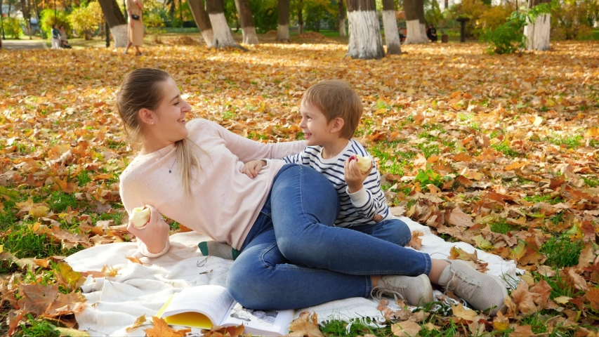 4k footage of smiling and laughing little boy with young mother lying on blanket at autumn park and eating apples | Shutterstock HD Video #1043265076