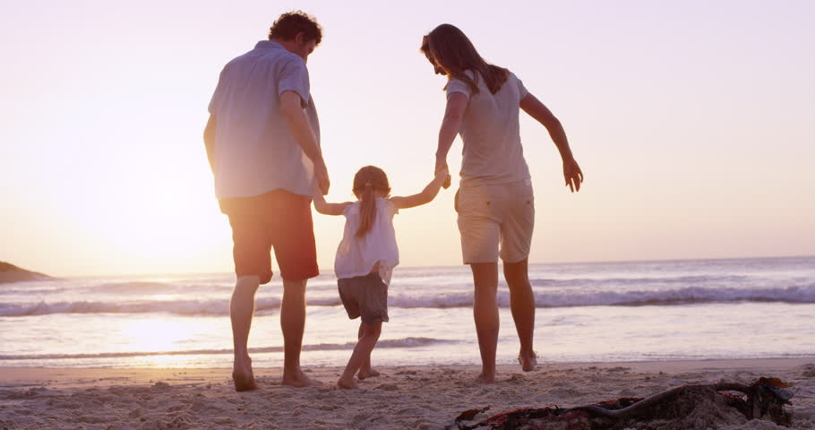 Happy family on the beach holding hands swinging little girl around at sunset on vacation slow motion RED DRAGON | Shutterstock HD Video #10437746