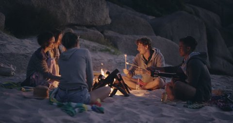 Beach Party at sunset with bonfire and roasting marsh mellows with friends RED DRAGON