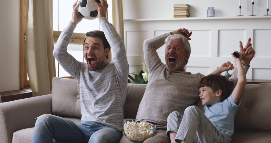 Excited three generation men family grandson young father and old grandfather fans hold soccer ball remote control watch tv sport game celebrate goal television team victory in tv match sit on sofa | Shutterstock HD Video #1044003436