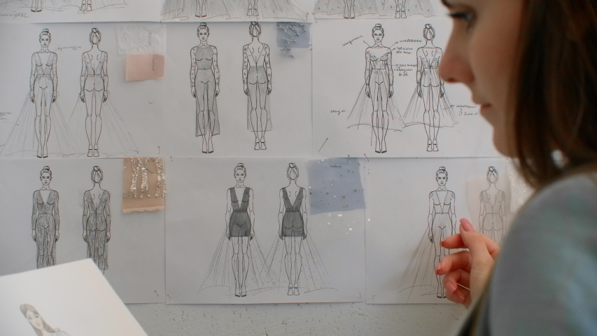 Female fashion designer is choosing and hanging clothing sketches to wall for her newest collection. Light fabrics. Female fashion designer is choosing | Shutterstock HD Video #1044678646
