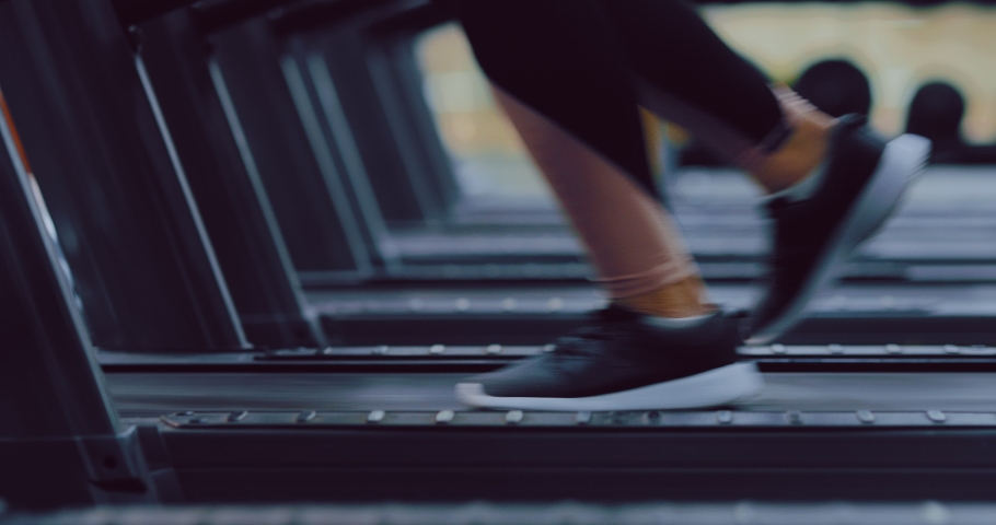 Female legs in sneakers run on a treadmill in the gym. Cardio exercises in a sports club. Close-up. | Shutterstock HD Video #1044742996