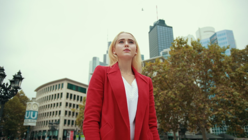 Young woman wearing white t-shirt and red jacket in modern city metropolis is standing at meeting place and nervously waiting, glancing at clock partner is late.