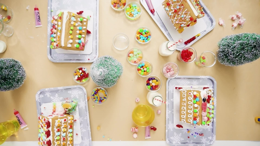 Flat lay. Step by step. Kids decorating small gingerbread houses at the Christmas craft party.   Shutterstock HD Video #1044886156