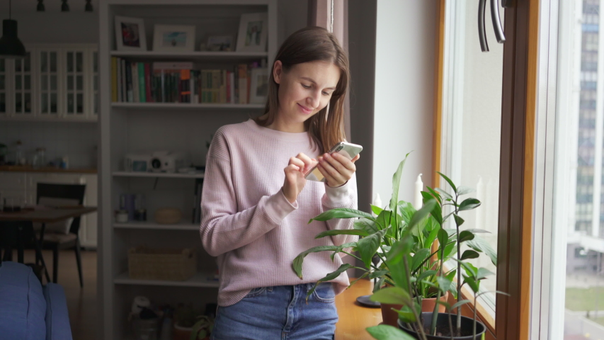 Close up young woman stands near the window at home use phone communication female message cellphone cheerful smile internet modern smartphone portrait. Texting browsing social media. 4k | Shutterstock HD Video #1044896566