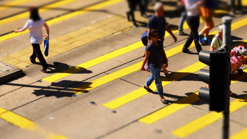 HONG KONG - NOV 2, 2017: Citylife of busy central district. Crowd of pedestrians walking in hurry on crosswalk on traffic light. Cars and buses driving on road. Time lapse. Tilt shift lens blur effect   Shutterstock HD Video #1044910366