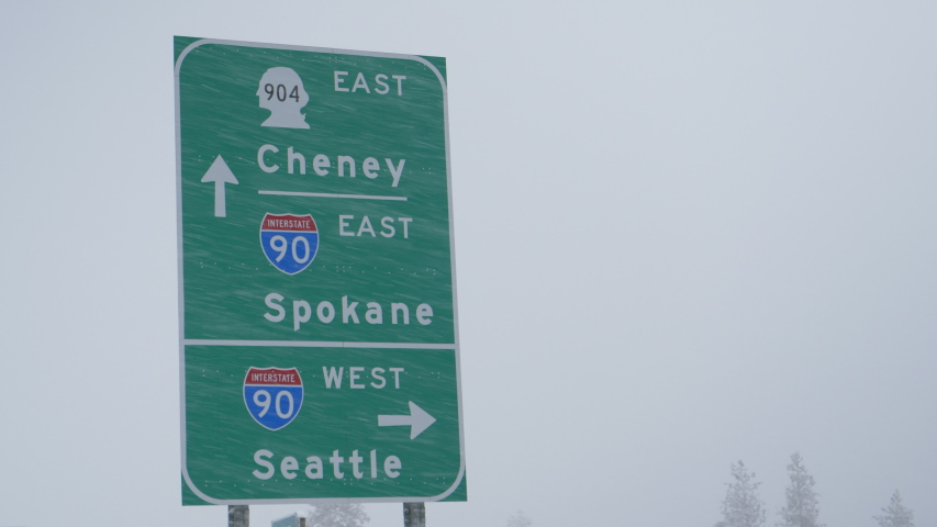 CLOSE UP: Green traffic sign directs traffic around the state of Washington during a snowstorm. Highway traffic sign weathers a blizzard engulfing the state of Washington. Arrows pointing to US cities | Shutterstock HD Video #1044956446