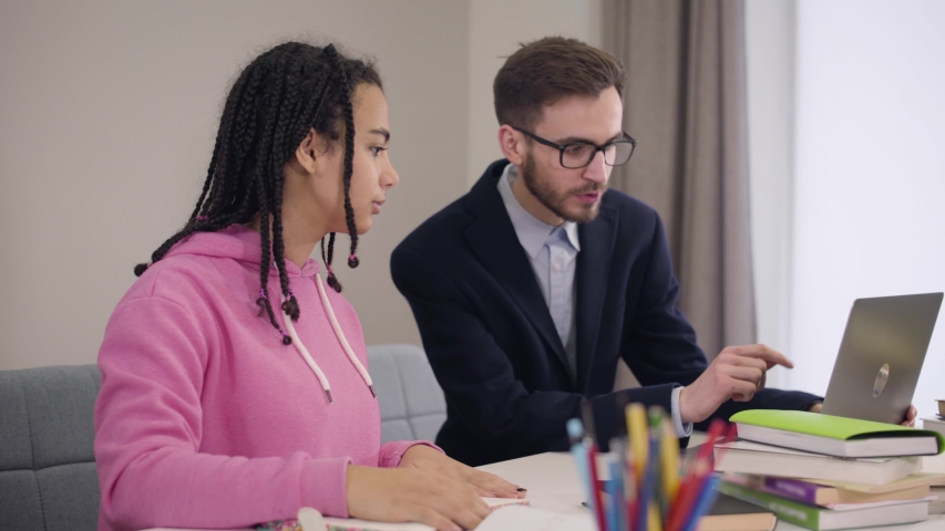 Portrait of confident Caucasian tutor in eyeglasses explaining material to young African American college student. Pretty girl with afro pigtails studying indoors. Education, learning, intelligence. | Shutterstock HD Video #1045058356