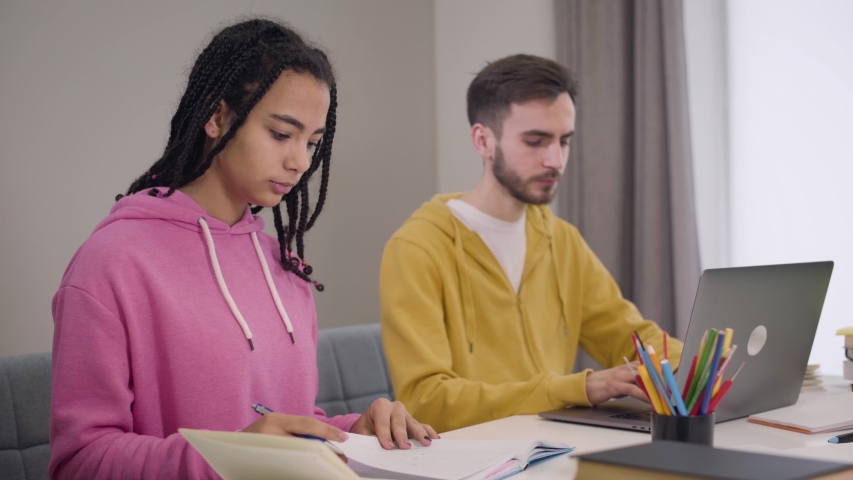 Side view of blurred Caucasian boy using laptop and asking for advice from beautiful African American girl. Groupmates studying together. Education, learning, intelligence. | Shutterstock HD Video #1045058386