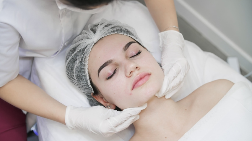 Close up of Woman's Face getting Face Massage in Beautiful Beauty Studio. Beautician making procedure with her Client. Girl with Attractive Appearance enjoying skin Massage | Shutterstock HD Video #1045089676
