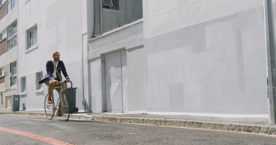 Side view of a young Caucasian businessman on the go in the city, riding a bike in the street, slow motion | Shutterstock HD Video #1045109656