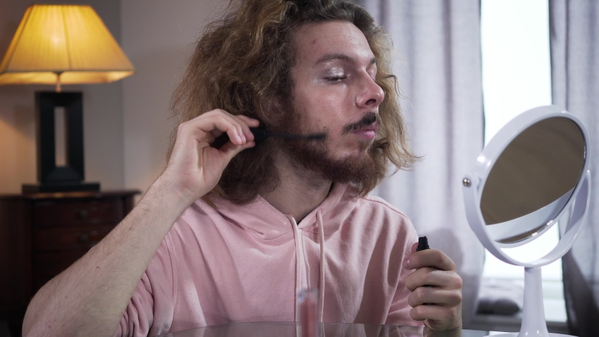 Portrait of adult Caucasian non-binary transgender with makeup applying mascara on beard. Self perception, gender identity, minority problems. | Shutterstock HD Video #1045123036