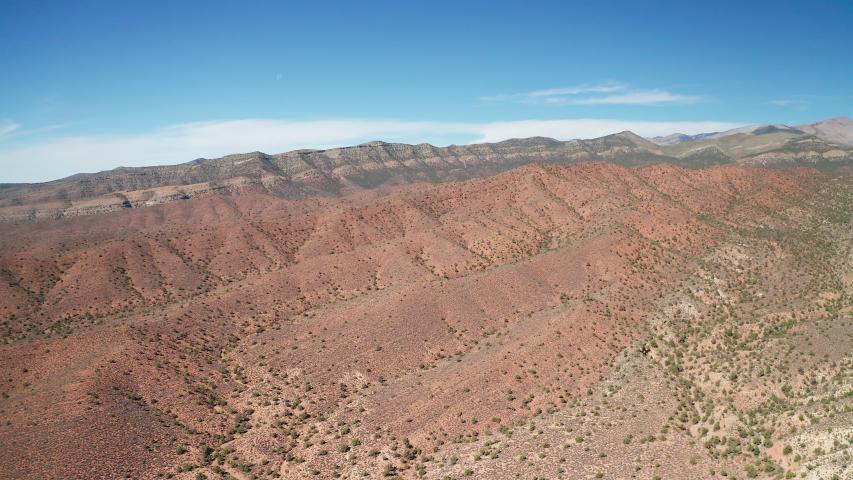 Aerial pull back shot of colorful red, orange, white desert landscape, greenery | Shutterstock HD Video #1045139716