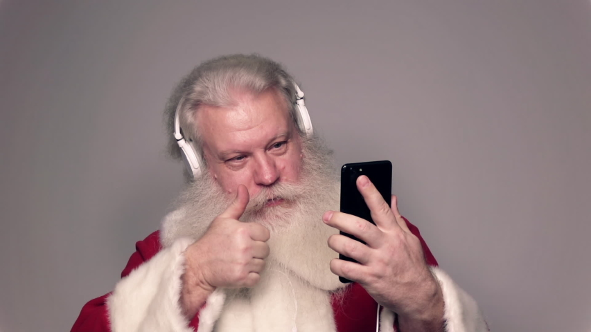 Senior Caucasian smiling man in Santa Claus suit with splendid grey hair, mustache and beard, talking on sell phone with funny expression. Funny portrait of handsome European merry people on white. | Shutterstock HD Video #1045169926