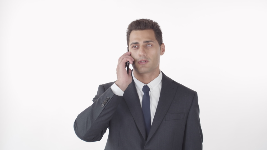 Medium shot of mixed-race businessman with dark hair wearing suit chatting on mobile phone on white background | Shutterstock HD Video #1045206256