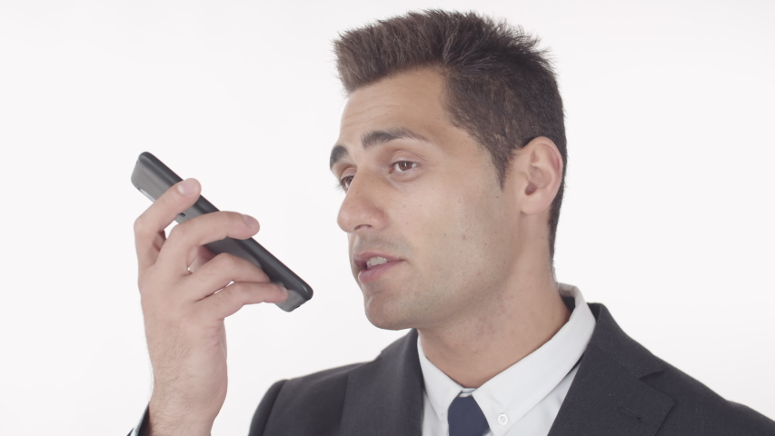 Close up of successful businessman with black hair wearing elegant suit standing on white background and recording voice message on smartphone | Shutterstock HD Video #1045207156