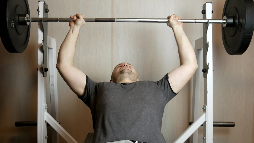 Handsome athletic man performs bench press on the bench in the gym. | Shutterstock HD Video #1045313566
