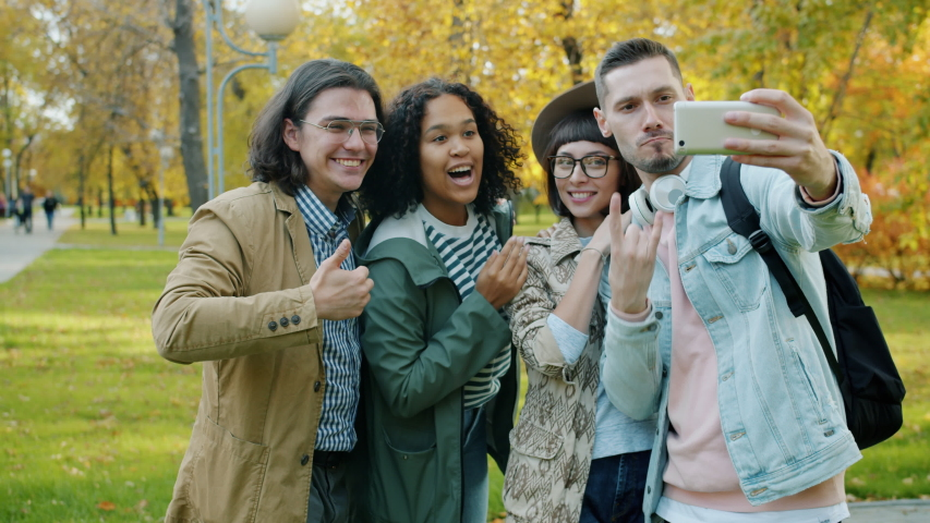 Laughing young people friends are taking selfie in park with smartphone camera showing thumbs-up hand gesture. Modern technology and friendship concept. | Shutterstock HD Video #1045402216