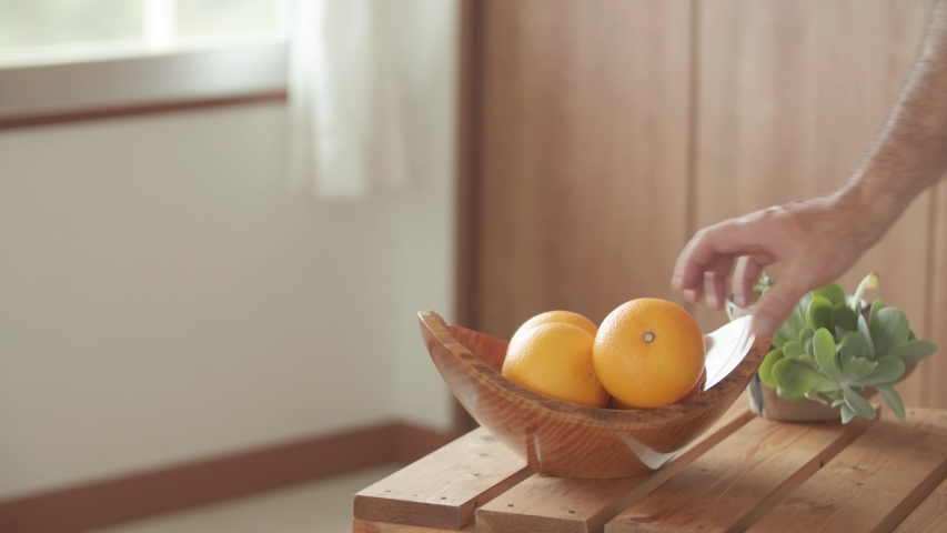 Taking an orange from a wooden bowl on a wooden table by hand | Shutterstock HD Video #1045451356