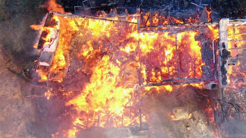 House burning to the ground, aerial top down view of flames engulfing the wooden structure | Shutterstock HD Video #1045500286