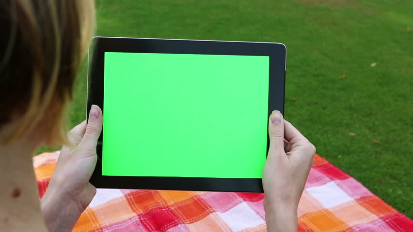 A woman uses a tablet PC at his desk. Chroma key screen for placement of your own content. Picnic summer weekend. Outdoor recreation. Video footage. Canon 24-70mm #10460636