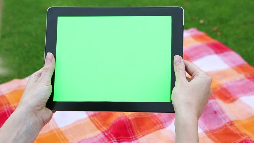 A woman holding a blank tablet PC with a green screen for your own custom content.  The static camera. Summer picnic. shallow depth of field, Video footage. Canon 24-70mm #10460696